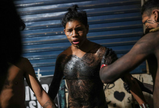 Guarani Mbya indigenous people paint their bodies black as they stay in an occupied area, after a protest against tree cutting and the construction of an apartment complex near Jaragua indigenous land in Sao Paulo