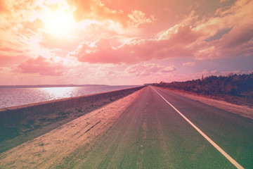 The highway on the dam along the sea. Landscape with a beautiful evening sky