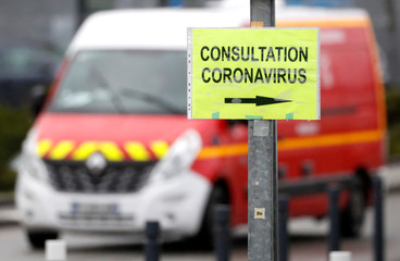 Placard for coronavirus disease (COVID-19) consultations is seen in front a fire truck at an entrance of the hospital in Vannes