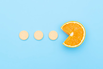Vitamin C supplements pills with Orange Fruit Cross Section isolated on blue background. Vitamin deficiency, avitaminosis concept. Homeopathy cure treatment, Healthy Lifestyle flat lay