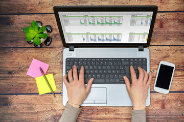Woman working at home on a laptop and entering numbers on a spreadsheet