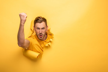 angry handsome man in yellow outfit in yellow paper hole showing fist