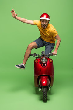 happy delivery man in yellow uniform and helmet doing trick on scooter on green