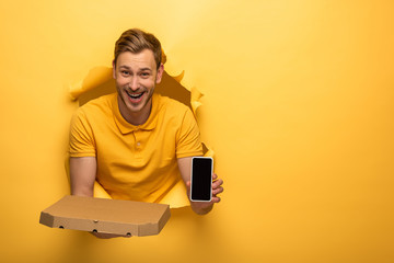 happy handsome man in yellow outfit holding smartphone and pizza box in yellow paper hole