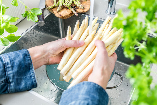 cropped shot of male hands in soil washing fresh asparagus in kitchen sink.