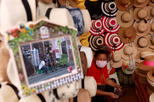 Vendors pass their time as they wait for customers at an empty tourist area, due to fear of the coronavirus in Phuket