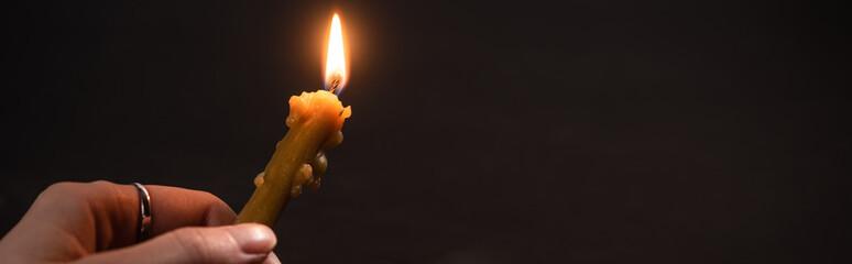 Fototapeta cropped view of woman holding burning church candle in dark, panoramic shot obraz