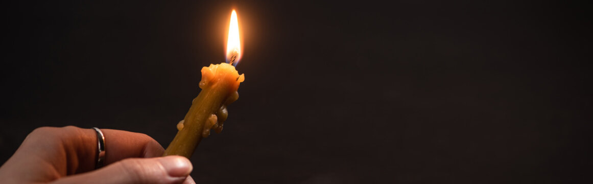 cropped view of woman holding burning church candle in dark, panoramic shot