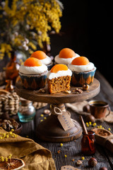 easter carrot cupcakes with white cream and slice of apricot on top (egg style decorated cupcakes) on wooden cake stand on rustic table with willow, oranges, nuts, spices