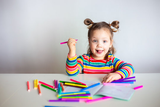 little girl drawing with color pencils