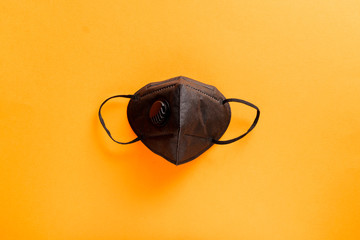 black medical mask on an orange background