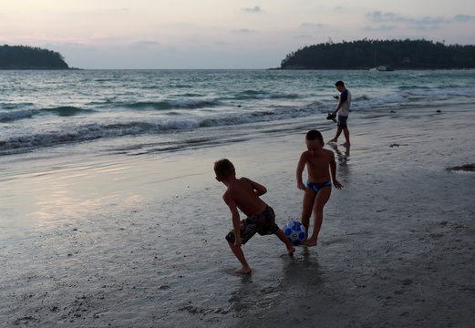 People play on a beach which is usually full of tourists, amid fear of coronavirus in Phuket