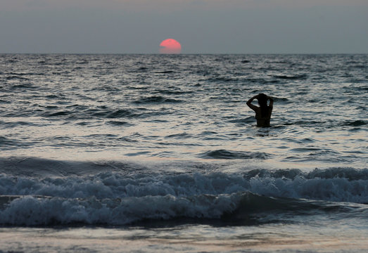 A person is seen in water near a beach which is usually full of tourists, amid fear of coronavirus in Phuket