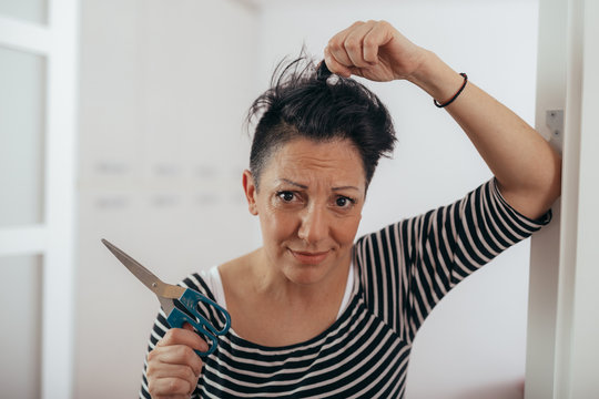 doubt and thoughtful mid aged woman holding scissors for cutting her hair