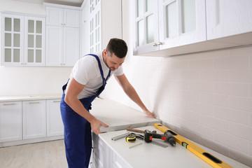Worker installing new countertop in modern kitchen