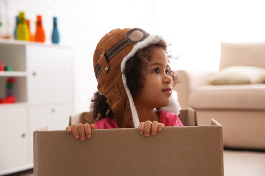 Cute African American child playing with cardboard box at home