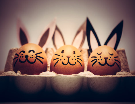 Three painted smiling Easter eggs bunnies sitting in an egg carton.