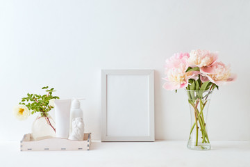 Home interior with decor elements. White frame, pink peonies in a vase, interior decoration