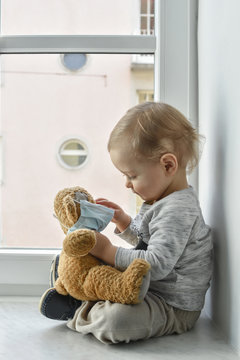 Child in home quarantine playing at the window with his sick teddy bear wearing a medical mask against viruses during coronavirus COVID-2019 and flu outbreak. Children and illness disease concept.