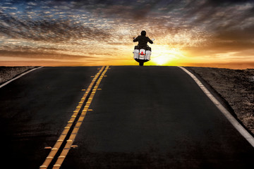 Motorcycle rider on street riding toward sunset sky Wall mural
