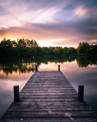 A wooden jetty on a lake at sunset