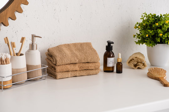 Shelf with hygiene objects near towels, beauty products and flowerpot in bathroom, zero waste concept
