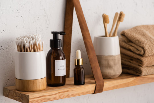 Selective focus of hygiene and cosmetic products with towels on shelf in bathroom, zero waste concept
