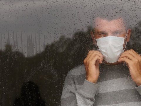 Male in medical mask looking through window in a sad rainy day. Copy space.