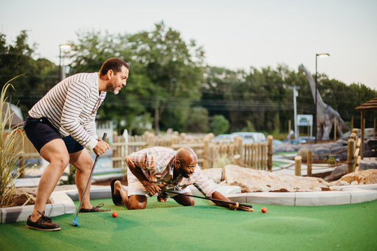 Friends playing golf together at miniature golf course