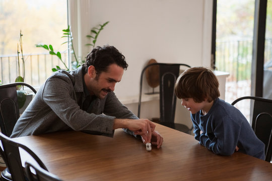 Father and son playing with dreidel on dining table at home