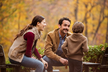 Happy parents spending leisure time with son in backyard during autumn