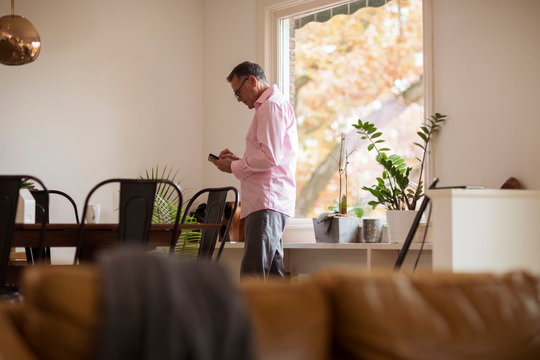 Side view of mature man using mobile phone while standing at home