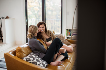 Smiling mid adult woman talking with mother while sitting on sofa at home