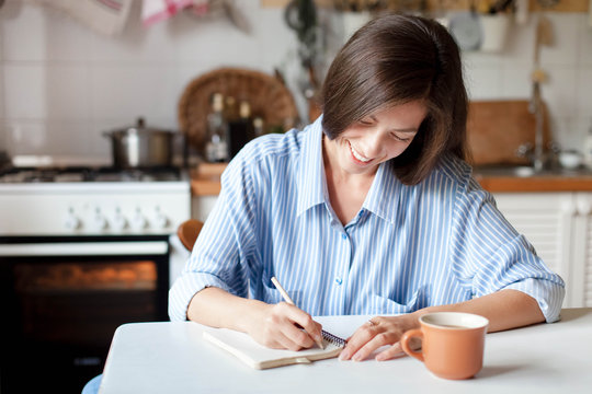 Young woman writting notes in paper notebook. Happy girl sitting at table with cup of coffee in cozy home kitchen. Concept of housekeeping, recipe, planning.
