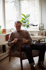 Mature man using mobile phone while sitting on chair at home