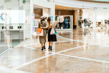 Shopping and entertainment, mall inside. Two beautiful girls with paper bags at the mall. The joy of consumption, Gift shopping, holiday.