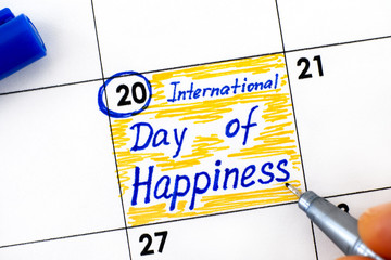 Woman fingers with pen writing reminder International Day of Happiness in calendar