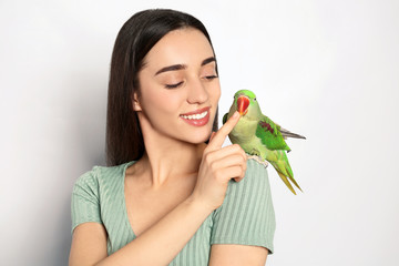 Young woman with Alexandrine parakeet on light background. Cute pet
