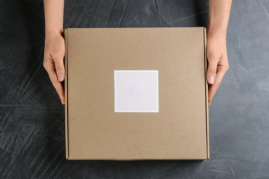 Woman holding cardboard box at grey stone table, top view