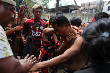 Guarani Mbya indigenous people do a ritual before leaving an area they occupied as a protest against tree cutting and the construction of an apartment complex near Jaragua indigenous land, after an eviction order, in Sao Paulo