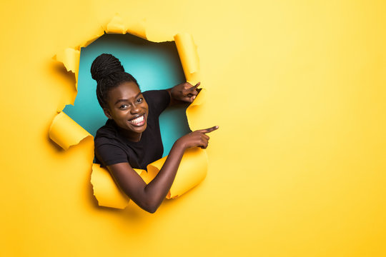 Young african woman pointed side and posing from yellow paper hole