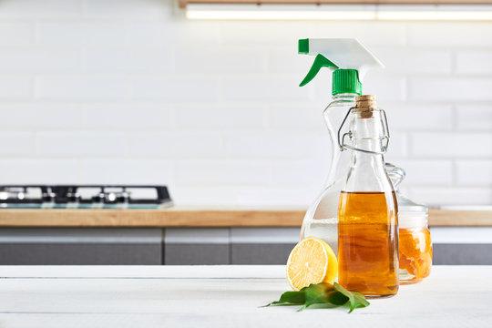Eco-friendly natural cleaners: baking soda, soap, vinegar, salt, lemon and brush on wooden table. Kitchen background.