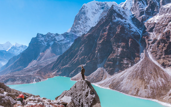 A man standing on the rock in front of turquoise Chola lake and  Tabuche foothills, from the way to Dzongla, Sagarmatha national park, Everest Base Camp 3 Passes Trek, Nepal
