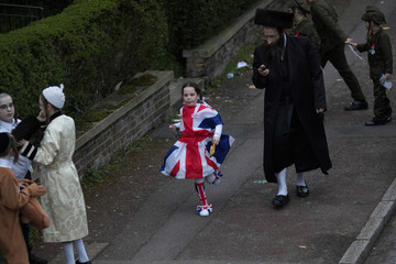 A Jewish girl in a Union Flag dress runs down the street during the annual holiday of Purim in Stamford Hill in London