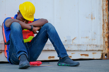 African worker man sit close to cargo container and he look tire and also sleepy.
