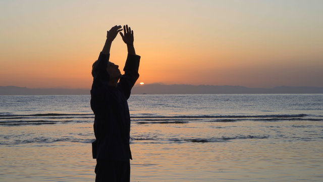 Silhouette of man practicing energy exercises at sunset by the sea