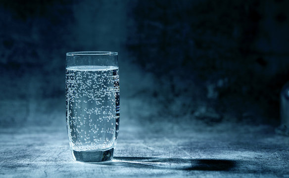 Glass of sparkling water on the grey background