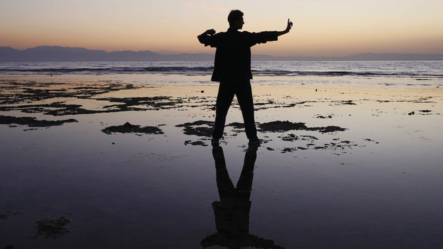 Silhouette man practices qigong exercises, working with qi energy, stand shallow.