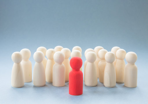 A leader or manager standing out from a crowd of co workers or team mates whilst inspiring them to a success