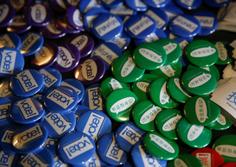Vote buttons in different languages sit on a table at the King County Elections ballot processing center during the presidential primary in Renton